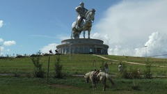 Horses and people walking on the background of a monument to Genghis Khan. Stock Footage