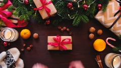 Top hands Santa Claus adjusts a red ribbon on a gift. Stock Footage