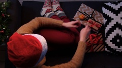 Top view girl at home sitting on the couch unwrapping a Christmas present. Stock Footage