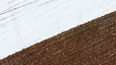 Amazing aerial view of tractor tilling snow covered field in Winter Stock Footage