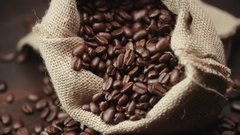 Quality of grain roasted coffee to spill from the bag jute , slow motion Stock Footage