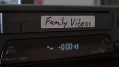 VHS Family Video Tape being put into Old VCR Close Up. Stock Footage