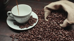 Pouring a Cup of hot coffee and roasted coffee beans on the table, slow motion Stock Footage
