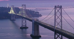 Aerial of San Francisco Bay Bridge at sunrise sunset and night Stock Footage