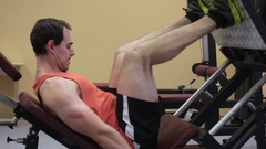 Close-up of man in gym training at leg press. Stock Footage