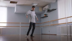 Handsome male dancer in grey pullover and black trousers dancing in the center Stock Footage