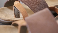 Female open-toed leather flip-flops seams and parts Stock Footage