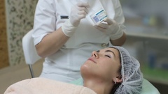 Cosmetologist making cosmetic facial mask to the client at the cosmetology Stock Footage