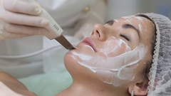 Woman cleaning skin on beautiful client face in beauty salon Stock Footage