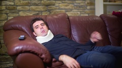 Man with neckbrace watching TV spinal injury Stock Footage