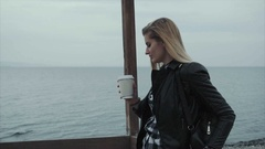 Attractive blond woman wearing black leather jacket drinking coffee near the sea Stock Footage