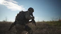 Airsoft soldier with a rifle and full NATO ammunition running and aiming Stock Footage