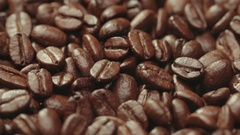 Beautiful background of roasted steaming coffee beans which rotate in slow Stock Footage