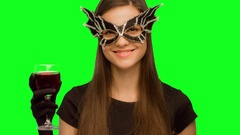 The girl in the mask and black dress drink wine. and enjoys Stock Footage