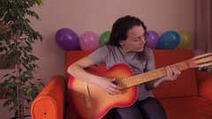 A girl playing on an acoustic guitar Stock Footage