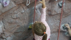 Rock climbing. Little girl climbing on training wall in climbing center.Sports Stock Footage