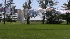 Clothes drying on clothes line in backyard on summer day Stock Footage