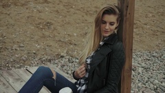 Young blond pretty woman sitting on wooden pier and resting Stock Footage