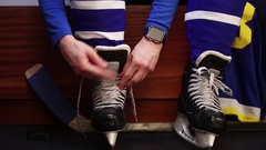 Hockey player lacing skate and checking pulse on smartwatch before training. Stock Footage