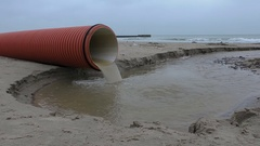 Storm drain water flowing from the plastic pipe to the sea Stock Footage