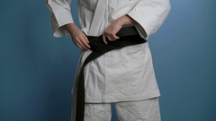A woman putting on black karate belt Stock Footage