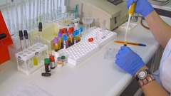 Female scientist working with test tubes, pipette and testing blood samples in Stock Footage