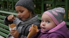 Two sisters sitting on the bench and eating ice-cream. Little girls sit Arkistovideo