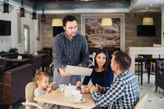 Restaurant and holiday concept - waiter giving menu to happy family at cafe Stock Photos