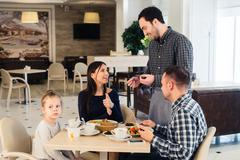 Friendly smiling waiter taking order at table of family having dinner together Stock Photos