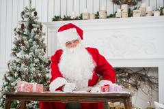 Portrait of Santa Claus answering Christmas letters Stock Photos