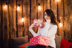 Young happy beautiful woman with gift boxes sits near wall decorated for Stock Photos