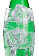 Bottle and glass with healthy sparkling  water with ice cubes on white Stock Photos
