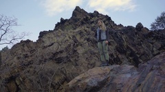 Adventurous Young Woman Looks At Mountain Views From Atop A Boulder Stock Footage
