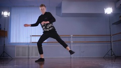 Handsome hip-hop dancer dressed in black trousers and pullover performing Stock Footage