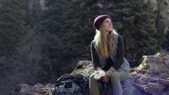 Adventurous Young Female Backpacker Rests On Boulder, Takes Break, Enjoys Views Stock Footage