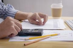 Close up of Business man working calculating on financial report at the office Stock Photos