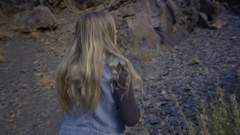 Young Woman Walks (Away From Camera) And Climbs Atop Boulder, Looks Out At View Stock Footage
