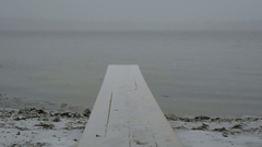 Girl jumping and waving on the shore of the lake on the bridge. Happy winter  Stock Footage