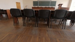 Conference hall with brown desks, soft black chairs, blackboard and podium Stock Footage