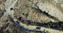 AERIAL: Trucks Driving on Dirt Road Curve Stock Footage