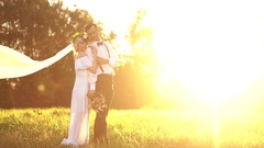 Bride and groom walking outdoors at sunset Stock Footage