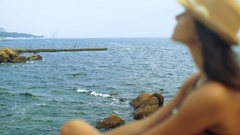 Young happy woman sitting on the stone and looking at the waves on the sea Stock Footage