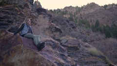 Young Woman Sits On A Boulder In Mountains Of Utah, She Looks Around At Beauty Stock Footage