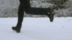 The girl runs on the road in the winter forest. Feet closeup from below Stock Footage