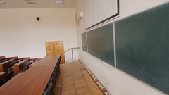 Empty lecture auditorium, green blackboard, wooden furniture on several levels Stock Footage