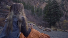 Young Woman Drinks Her Morning Coffee, Enjoys Views Of Nature From Sleeping Bag Stock Footage