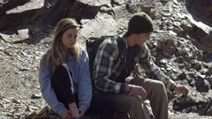 Outdoorsy Couple Sit On Boulder, Prepare To Rock Climb, Put On Climbing Shoes Stock Footage