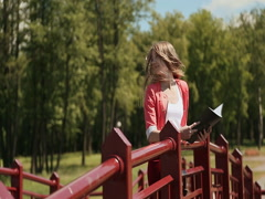 Young beautiful girl reading a book in a green Park on the bridge. Blond hair in Stock Footage