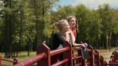 Beautiful young girl on a bridge in green park and talk and enjoy nature. Sunny Stock Footage