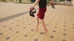 Beautiful girl businesswoman barefoot with shoes and a folder in his hands after Stock Footage